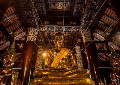 Golden Buddha statue in a temple with several symatric ropes