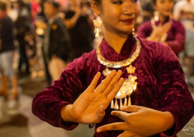 Focus on the hands of a Thai dancer performing at night with a purple dress