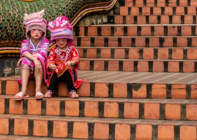 Hmong children dressed in traditional pink costumes and sitting on the stairs of a temple