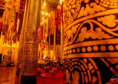 Inside buddhist temple between golden columns with monks praying in front of a tall golden buddha