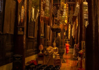 Inside a Buddhist temple with a monk walking away in the background