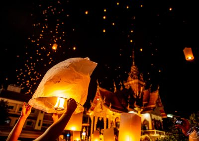 Person releasing a thai lantern at night during Yi Peng festival with a temple in background