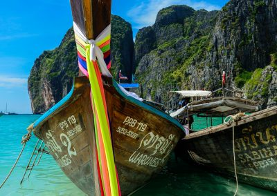 Thai long-tail boat in the turquoise sea, taken from below, with colorful ribbons in the foreground