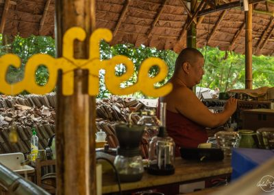 Monk preparing a coffee at a bar with a coffee sign written in yellow