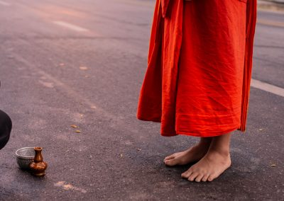 Feet of a monk in the street facing an offering