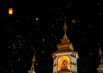 Night sky with golden and white top of temple with a Buddha and thai lanterns floating in the sky in the background