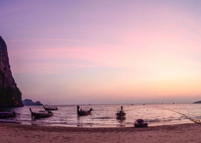 Panoramic picture of purple sunset on the beach with cliff on the left