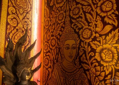 Red column with goddess painted in gold in a temple in Chiang Mai