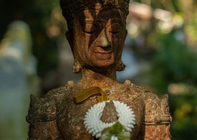 Statue in a forest with shadow of leaf on the face and holding a real bracelet in pearls
