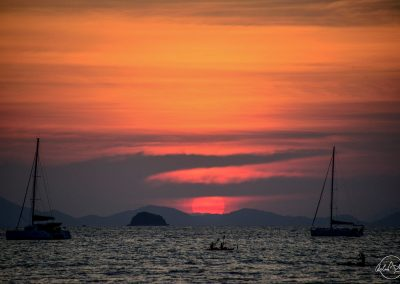 Sunset with huge round red sun reaching sea level; shadows of sailing ships and kayak in the foreground