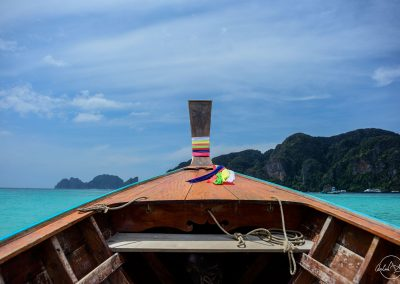 Inside of a small Thai boat on turquoise sea with an island in the background