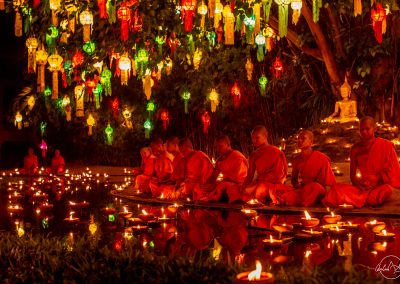 Close up of monks sitting in Wat Phan Tao temple at night in the middle of the candles and colorful lanterns in the trees and facing the river with reflections
