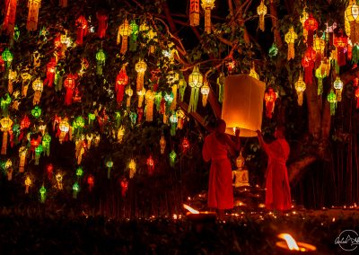 2 monks holding a lantern with temple at night in the middle of the candles on the floor and colorful lanterns in the tree in the background