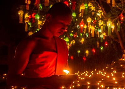 Young monk at night holding a candle and walking with background full of colorful lights and lanterns