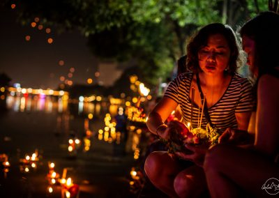 Young woman holding flowers and candles at night for loy kratong and sitting near the river