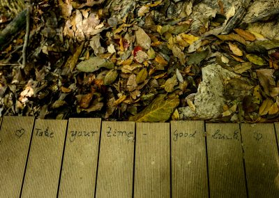 """Wooden board of a hiking trail with """"take your time…good luck"""" hand written"""