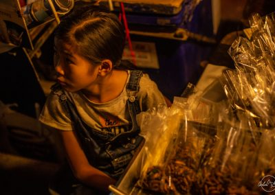 Portrait of a young girl in a jumpsuit sitting at a market stall at night