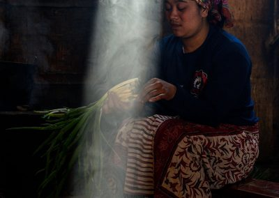 Portrait of an Indonesian woman cutting vegatables on a bench in a room and low light with a ray of light from the roof highlighting her face