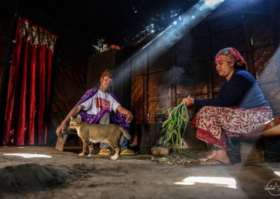 Indonesian couple sitting inside witon two benches with cat on the floor in the middle