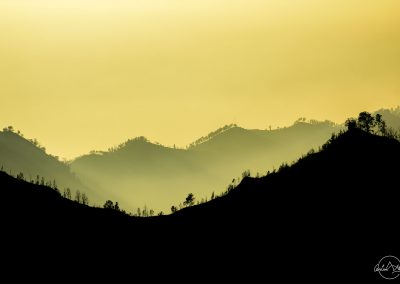 Silhouettes of hills in yellow sky background