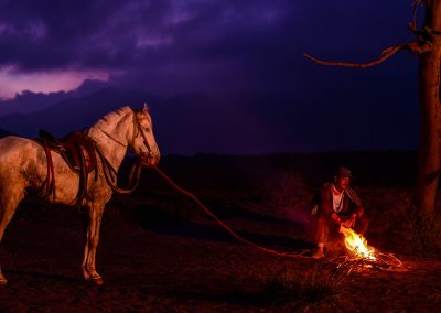 Horseman sitting on the ground next to white horse and fire at night