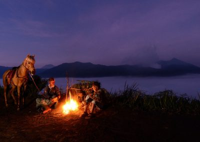 Man and boy with a horse sitting on the ground with a fire in front of them and volcano and night sky in background