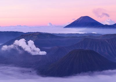 Zoom on Mount Bromo surrounded by clouds with a purple and orange sunrise light