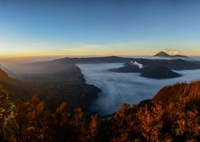 Panoramic view of Mount Bromo just after sunrise with yellow and blue hue