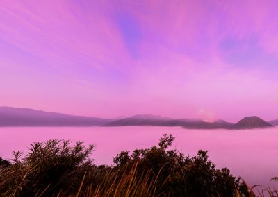 Panoramic view of purple and pink sunrise above volcano