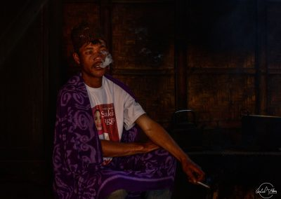 Portrait of an Indonesian man smoking and blowing smoke in a room with low light