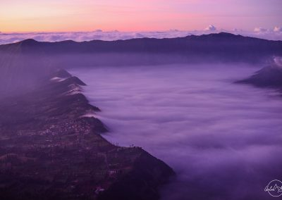 Wide and thick white clouds slowly taking away from cliffs with small villages in purple early morning hue