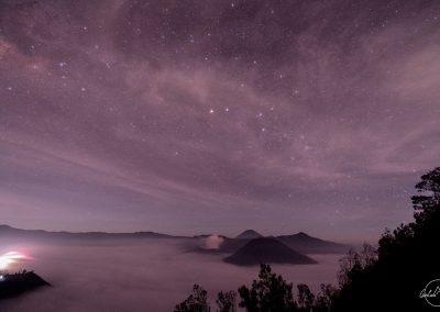 Purple sky full of stars above volcano