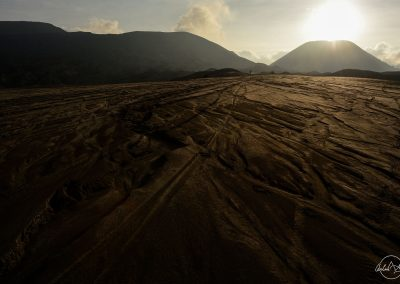 Desert of sand in the shadow surrounded by volcano and hills with sun setting in background