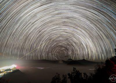 Stars trail creating multiple circles around Mount Bromo at night