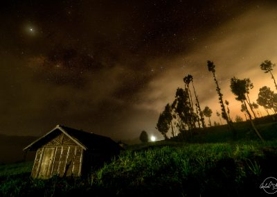 Wooden hut in a field at night with sky full of stars and yellow halo of light on the right