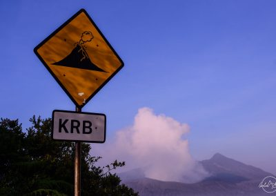 Yellow sign with a volcano in eruption painted on it, blue sky and white clouds in the background