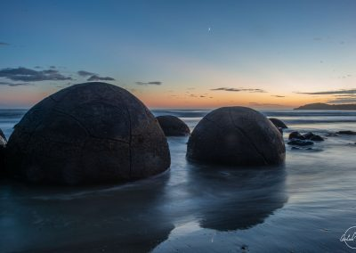 Two boulders on the beach in the water facing beginning of sunrise
