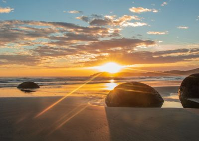 Group of boulders with the sun rising and yello and blue sky
