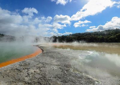 Panoramic view of hot springs, champagne pool on the left surrounded by orange color and on the right a yellow pool