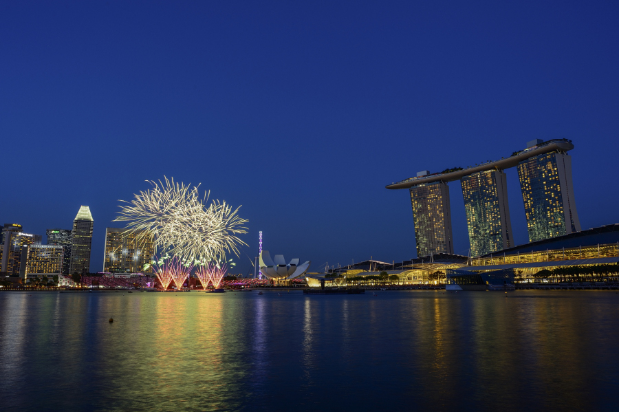 Firework on the left with Marina Bay Sand on the right and dark vivid blue sky