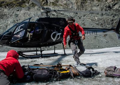 Man in a red jacket packing bags on a glacier with helicopter waiting in background