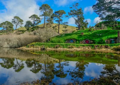 Small hobbit houses with red and blue doors along the river at the bottom of a hill