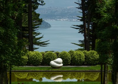 White abstract sculpture at the end of a green corridor with blue water at the very far end