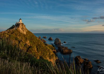 Lighthouse at the end of a path on top of a small hill facing the sea and the sunset