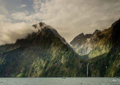 Tall and pointy mountains stepping out of a lake and covered by clouds
