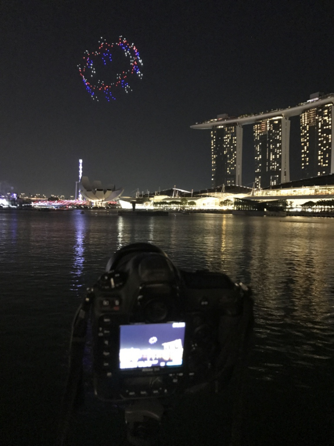 Nikon D4 camera on a tripod at night in front of Marina Bay Sand and fireworks
