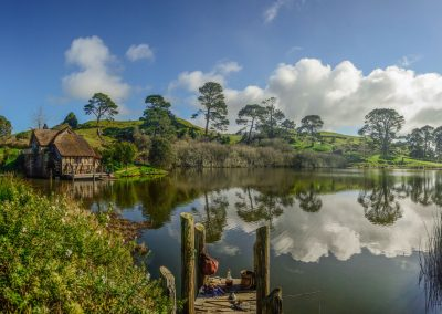 Panoramic view of Hobbiton with small bridge and house on the left of the river, picnic bags on the floor in the middle