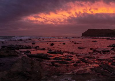 Panoramic view of a sunset of the sea with rocks in the foreground and red and pink sky