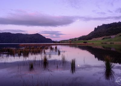 Purple sunset over a lake with reflection of hills and moon in the water