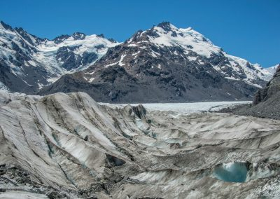 Middle of a glacier surrounded by snowy mountains with blue sky